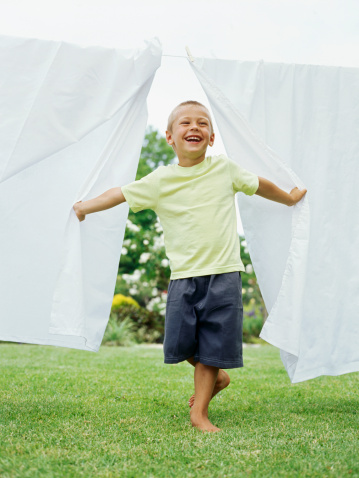 Boy standing between sheets hanging on a clothesline