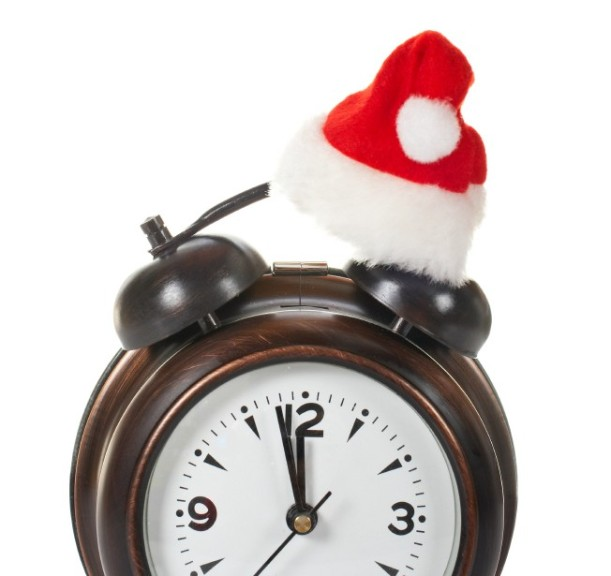 Partial view of alarm clock with christmas hat, isolated over white background
